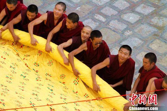 """藏語""""雪""""為酸奶,""""頓""""意為宴,所以這一節日也被稱為""""酸奶節""""。圖為2018年拉薩哲蚌寺僧人合力展開巨幅釋迦牟尼佛唐卡。(資料圖)趙朗攝"""