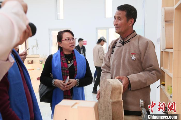 图为乌力吉(右)为来访嘉宾介绍马头琴。受访者供图