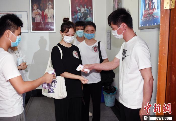 福建省实验闽剧院工作人员对参加选拔活动的青年戏曲演员进行体温检测。 记者刘可耕摄