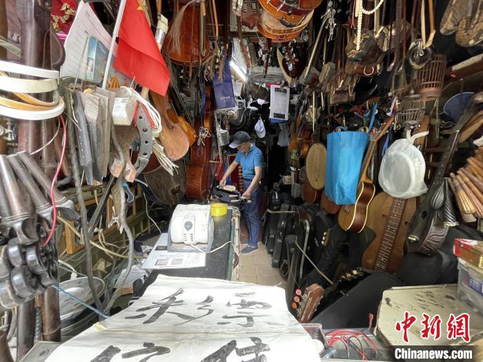 小店的顶部、墙壁等处密密麻麻地挂着冯顺成的乐器宝贝,足有上百把琴。 康玉湛摄