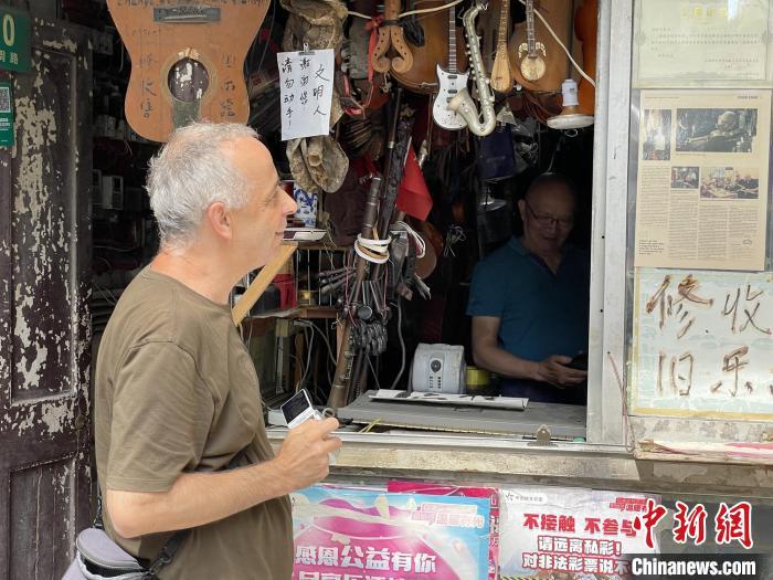 """冯顺成的小店""""火""""到了海外,慕名而来的人数不胜数。 康玉湛摄"""